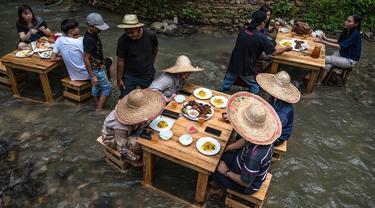 Pelanggan menikmati makan siang di restoran dengan meja di tengah aliran sungai di Kampung Kemensah di pinggiran Kuala Lumpur, Malaysia, Selasa (14/7/2020). Konsep restoran ini cukup unik, memadukan pemandangan air sungai dan pepohonan hijau yang menyegarkan. (Photo by Mohd RASFAN / AFP)