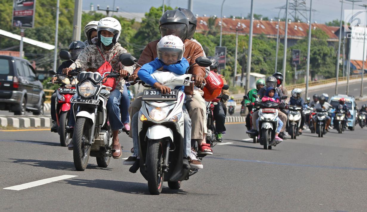 Pemudik sepeda motor melintas di Jalur Pantura, Jawa Barat, Minggu (2/6/2019). Sejumlah pemudik sepeda motor terpantau mengabaikan keselamatan dengan membawa barang bawaan dan penumpang melebihi kapasitas. (Liputan6.com/Herman Zakharia)