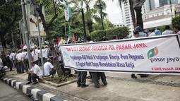 Massa dari SP PD Pasar Jaya membentangkan spanduk dalam unjuk rasa di Balai Kota DKI Jakarta, Rabu (31/1). Mereka menuntut untuk menghentikan rekrutmen tenaga profesional yang melanggar peraturan Pasar Jaya SK 65 Tahun 2016. (Liputan6.com/Faizal Fanani)