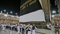 Petugas saat mengganti kain penutup Ka'bah (Kiswah) dengan yang baru di Masjidil Haram, kota suci Makkah, Arab Saudi (18/7/2021). Menjelang puncak ibadah haji 1442 H, petugas Masjidil Haram melakukan penggantian kain penutup Ka'bah lama dengan Kiswah yang baru. (AFP Photo)