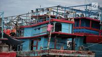 Sejumlah nelayan memperbaiki kapal di Pelabuhan Muara Angke, Jakarta, Kamis (27/12). Nelayan tidak bisa melaut akibat gelombang tinggi sejak sebulan belakangan. (Liputan6.com/Faizal Fanani)