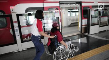 Petugas membantu penyandang disabilitas naiki ke kereta Lintas Rel Terpadu (LRT) di Stasiun LRT Veldrome, Jakarta, Sabtu (27/4). Kegiatan yang diikuti Jakarta Barrier Free Tourism (JBFT) itu untuk mengenalkan LRT lebih dekat, terutama kepada penyandang disabilitas. (Liputan6.com/Faizal Fanani)