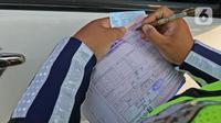 Polisi menilang pengendara di kawasan Fatmawati, Jakarta, Senin (10/8/2020). Ditlantas Polda Metro Jaya kembali menerapkan sanksi tilang terhadap kendaraan roda empat yang melanggar peraturan ganjil genap di masa Pembatasan Sosial Berskala Besar (PSBB) transisi. (Liputan6.com/Herman Zakharia)