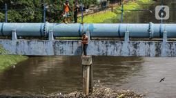 Petugas PPSU membersihkan sampah yang tersangkut di tengah derasnya aliran Kali Ciliwung, Jakarta, Rabu (19/5/2021). Pembersihan tersebut dimaksudkan agar tidak ada penumpukan sampah dan sedimentasi saluran di sepanjang Kali Ciliwung. (Liputan6.com/Faizal Fanani)