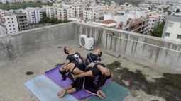 Instruktur yoga dari Zona Yoga Anahata melakukan gerakan yoga menjelang Hari Yoga Internasional di teras sebuah bangunan di Hyderabad, India pada 18 Juni 2020. Hari Yoga Internasional atau International Day of Yoga diperingati setiap tahun pada 21 Juni. (Photo by NOAH SEELAM / AFP)