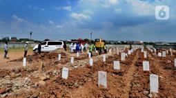 Petugas menurunkan jenazah korban COVID-19 dari ambulans untuk dimakamkan di TPU Rorotan, Cilincing, Jakarta Utara, Kamis (29/4/2021). Dalam sehari, TPU Rorotan memakamkan korban COVID-19 dengan rata-rata 5 hingga 8 jenazah. (merdeka.com/Arie Basuki)