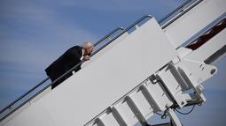 Presiden AS Joe Biden saat menaiki Air Force One di Pangkalan Udara Andrews, Maryland, Jumat (19/3/2021). Biden awalnya menaiki anak tangga dengan lancar tetapi sekitar setengah jalan menuju pesawat kepresidenan, dia tiba-tiba tersandung. (Eric BARADAT/AFP)