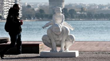 Seorang pria berjalan di samping patung karya seniman China Xu Hongfei di Thessaloniki, Yunani, Rabu (19/12). Sebanyak 15 patung karya Xu Hongfei menghiasi tepi pantai Thessaloniki. (Sakis Mitrolidis/AFP)
