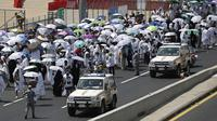 Kendaraan polisi melintas dekati ribuan umat muslim di salah satu jalan di Mina, Arab Saudi, Kamis (24/9/2015). Sekitar 310 jemaah wafat akibat berdesak-desakan saat prosesi lempar jumrah di Mina. (REUTERS/Ahmad Masood)