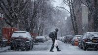 Seorang pria berjalan saat badai salju di Brooklyn di New York City (7/3). Badai salju kedua yang melanda New York dalam waktu seminggu ini diperkirakan akan membawa angin kencang. (Drew Angerer/Getty Images/AFP)