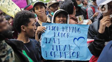 Warga Tanjung Priok membawa poster bertulis 'Priok Memang Kotor Tapi Tidak Koruptor' saat berunjuk rasa di depan Gedung Kemenkumham, Jakarta Selatan, Rabu (22/1/2020). Mereka menuntut Menkumham Yasonna Laoly minta maaf atas ucapannya yang menyinggung warga Tanjung Priok. (Liputan6.com/Faizal Fanani)