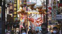Orang-orang yang memakai masker berjalan di bawah pernak-pernik Imlek saat melintasi Chinatown di Yokohama, Prefektur Kanagawa, dekat Tokyo, Selasa (9/2/2021). Yokohama Chinatown adalah kawasan pecinan terbesar di Jepang, terletak di pusat kota Yokohama. (AP Photo/Koji Sasahara)