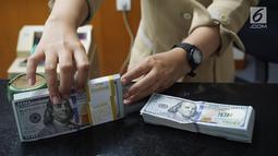 Teller menunjukkan mata uang dolar AS di penukaran uang di Jakarta, Rabu (10/7/2019). Nilai tukar rupiah terhadap dolar Amerika Serikat (AS) ditutup stagnan di perdagangan pasar spot hari ini di angka Rp 14.125. (Liputan6.com/Angga Yuniar)