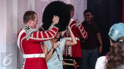 Seorang pasukan Scotts Guard alias penjaga Istana Inggris memakaikan topi berbulu ke warga yang ingin berselfie, usai beraksi di sela kegiatan Car Free Day (CFD) di kawasan Bundaran HI, Jakarta, Minggu (5/6). (Liputan6.com/Faizal Fanani)
