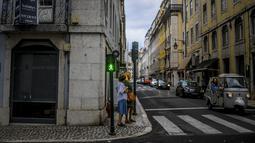 Dua orang menunggu untuk menyeberang jalan di pusat kota Lisbon, Portugal, Senin (13/9/2021). Portugal hari ini mengakhiri aturan wajib penggunaan masker di jalan-jalan. (PATRICIA DE MELO MOREIRA / AFP)