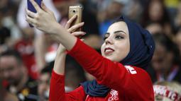 Fans wanita bermain ponsel sebelum pertandingan Piala Super Eropa 2019 antara Liverpool melawan Chelsea di Besiktas Park, Istanbul, Turki (14/8/2019). Dalam pertandingan ini Liverpool menang atas Chelsea lewat drama adu penalti 5-4 (2-2). (AP Photo/Thanassis Stavrakis)