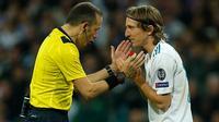 Pemain Real Madrid Luka Modric melakukan protes terhadap wasit saat melawan Bayern Munchen dalam pertandingan semifinal Liga Champions di stadion Santiago Bernabeu, Spanyol (1/5). (AP/Paul White)