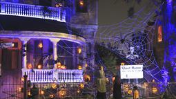 """Para pejalan kaki mengamati """"Rumah Hantu"""" (Ghost Manor) di New Orleans, Louisiana, 26 Oktober 2020. Untuk menyambut perayaan Halloween, sebuah rumah khusus di New Orleans disulap menjadi rumah hantu oleh pemiliknya. (Xinhua/Lan Wei)"""