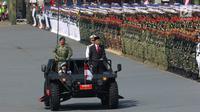 Presiden Joko Widodo (Jokowi) meninjau pasukan pada Upacara Peringatan HUT ke-72 TNI di Dermaga Indah Kiat Merak, Cilegon, Banten, Kamis (5/10). Jokowi bertindak sebagai inspektur upacara dalam peringatan itu. (Liputan6.com/Angga Yuniar)
