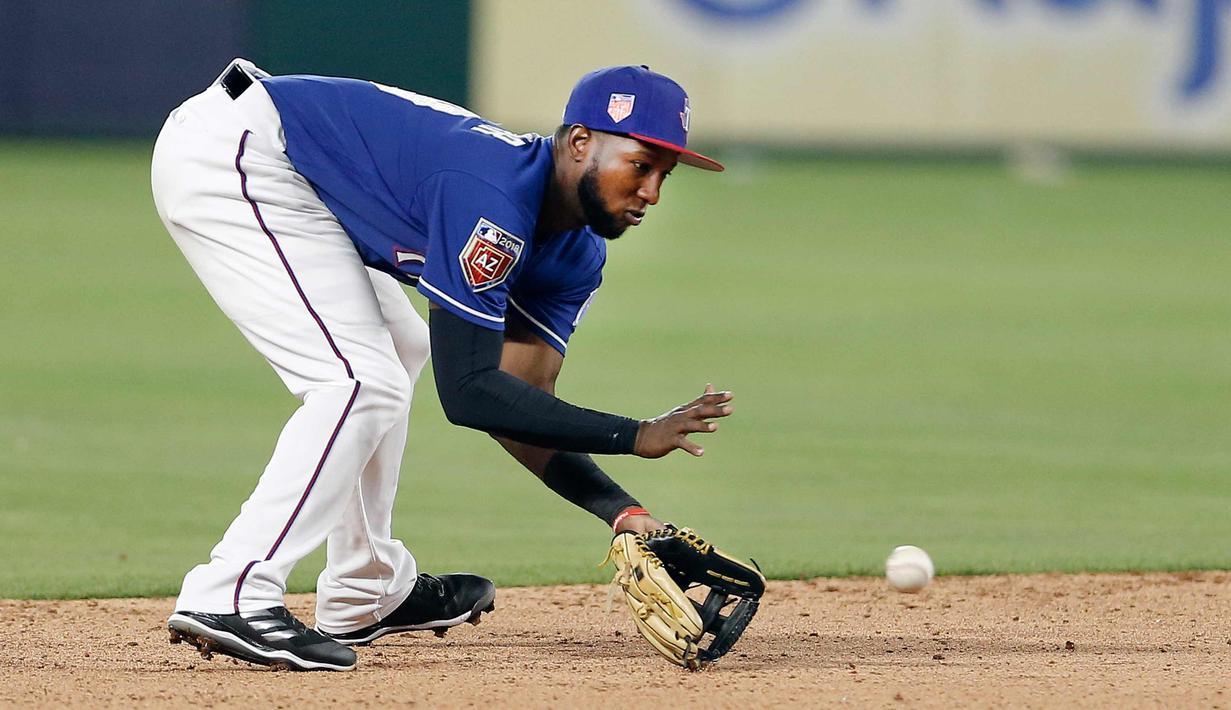Pemain Texas Rangers, Jurickson Profar (19) berusaha menangkap bola pukulan grounder Cincinnati Reds, Tony Cruz selama inning ketujuh pertandingan bisbol pramusim di Arlington, Texas (26/3). Texas menang 6-5. (AP Photo/Brandon Wade)