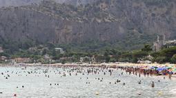 Orang-orang menyegarkan diri di laut di Palermo, Italia, Rabu (11/8/2021). Gelombang panas yang berkelanjutan akan berlangsung hingga akhir pekan dengan suhu diperkirakan mencapai lebih dari 40 derajat Celcius di banyak bagian Italia. (Alberto Lo Bianco/LaPresse melalui AP)