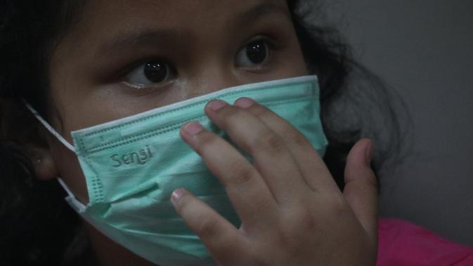 Seorang anak mengenakan masker untuk meminimalisir dampak kabut asap. (Dokumentasi BPNB)