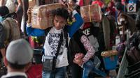Pemudik membawa barang miliknya di Stasiun Senen, Jakarta, Senin (19/6). Pada hari ini telah tercatat sebanyak 25.265 pemudik yang akan naik dari Stasiun Pasar Senen dan diperkirakan akan bertambah. (Liputan6.com/Gempur M Surya)