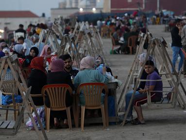 Suasana berbuka puasa saat bulan suci Ramadan di pantai Kota Gaza, Palestina, Kamis (21/5/2020). Di tengah pandemi COVID-19, berbuka puasa bersama di pantai Kota Gaza tetap ramai. (AP Photo/Adel Hana)