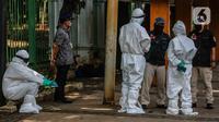 Tim medis menggunakan alat pelindung diri (APD) setelah memeriksa kondisi orang yang tergeletak di Jalan Merdeka Barat, Jakarta, Kamis (23/4/2020). Usai dilakukan pemeriksaan oleh tim medis, tunawisma tersebut dinyatakan negatif covid-19. (Liputan6.com/Faizal Fanani)