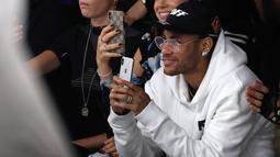 Pemain PSG, Neymar bermain ponsel saat menghadiri acara peragaan busana Off-White Spring-Summer 2019 Ready-to-Wear selama Paris Fashion Week, Prancis (27/9). Neymar tampil mengenakan jaket putih dan kaca mata emas. (AFP Photo/Francois Guillot)