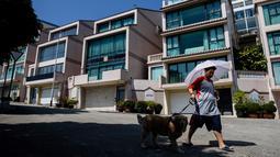 Pejalan kaki melintasi villa yang diyakini sebagai salah satu kediaman Kim Jong-nam di Macau, Kamis (16/2). Macau pernah menjadi rumah sekaligus tempat kakak tiri Kim Jong-un itu mencari uang selama pelarian dari rezim Korea Utara. (Anthony WALLACE/AFP)