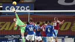 Kiper Everton, Jordan Pickford (kiri) terbang menepis tandukan gelandang West Ham United, Tomas Soucek (kanan) dalam laga lanjutan Liga Inggris 2020/21 pekan ke-17 di Goodison Park, Jumat (1/1/2021). Everton kalah 0-1 dari West Ham United. (AFP/Jan Kruger/Pool)