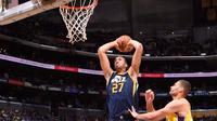 Center Utah Jazz, Rudy Gobert, melakukan dunk di hadapan center Los Angeles Lakers, Brook Lopez, pada laga pramusim NBA 2017/2018 di Staples Center, Los Angeles, Selasa (10/10/2017). (Bola.com/Twitter/NBA).