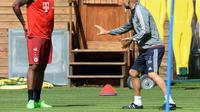 Pelatih Bayern Munchen Josep Guardiola memberikan instruksi kepada bek Jerome Boateng, dalam sesi latihan, di Munchen, 27 Juli 2015. (AFP PHOTO / CHRISTOF STACHE)