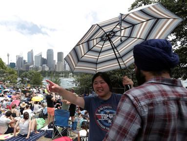 Ribuan warga duduk di lapangan untuk menonton kembang api jelang pergantian Tahun Baru di Sydney, Australia, (31/12/2016). Mereka sudah berada di taman sejak pukul 06.30 page waktu setempat. (REUTERS/Jason Reed)