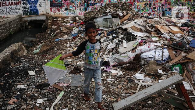 Seorang anak bermain di antara reruntuhan rumah di kawasan permukiman Jalan Pancoran Buntu II, Pancoran, Jakarta, Selasa (30/3/2021). Anak-anak yang tidak tahu permasalahan atas sengketa tanah menjadi korban dan terpaksa bermain di sisa reruntuhan tempat tinggal mereka. (Liputan6.com/Johan Tallo)