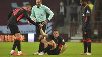 Pemain Liverpool James Milner (tengah) mendapat bantuan untuk berdiri dari rekannya Jordan Henderson saat melawan Aston Villa pada pertandingan putaran ketiga Piala FA di Stadion Villa Park, Birmingham, Inggris, Jumat (8/1/2021). Liverpool menang 4-1. (AP Photo/Rui Vieira)