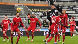 Bek Newcastle United, Ciaran Clark melepaskan sundulan sambil melompat ke gawang Liverpool dalam laga lanjutan Liga Inggris 2020/21 pekan ke-16 di St James' Park, Rabu (30/12/2020). Newcastle United bermain imbang 0-0 dengan Liverpool. (AFP/Stu Forster/Pool)