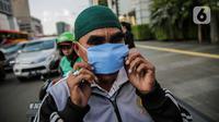 Warga mengenakan masker yang dibagikan relawan di Bundaran HI, Jakarta, Selasa (17/3/2020). Sebanyak 3.000 masker dibagikan gratis kepada pengguna jalan sebagai salah satu bentuk keprihatinan sekaligus berpartisipasi dalam upaya mencegah penyebaran virus corona COVID-19. (Liputan6.com/Faizal Fanani)