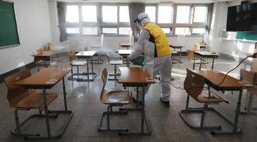 Petugas kesehatan mendisinfeksi ruang kelas untuk ujian masuk perguruan tinggi di Seoul, Korea Selatan, Selasa (1/12/2020). Sekitar 490.000 siswa lulusan sekolah menengah atas di Korea Selatan akan menjalani Tes Kemampuan Skolastik Perguruan Tinggi pada 3 Desember 2020. (AP Photo/Ahn Young-joon)