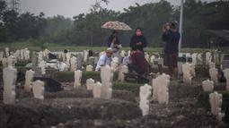 Keluarga berkumpul di dekat kuburan korban virus Corona Covid-19 di tengah hujan lebat di pemakaman Keputih, Surabaya (7/1/2020). Data Surabaya Lawan Covid-19 per 5 Januari 2021 menyebutkan, ada kenaikan 0.27 persen sehingga total kasus positif di Surabaya menjadi 18.399 kasus. (AFP/Juni Kriswanto)