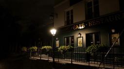 Restoran yang tutup di Montmartre di distrik 18 Paris, selama penerapan jam malam, Jumat (23/10/2020). Prancis memperpanjang jam malam untuk sembilan kota yang menjadikan sebanyak 46 juta orang harus berada di rumah mulai pukul 21.00-06.00 guna mencegah meluasnya virus corona. (Valery HACHE/AFP)
