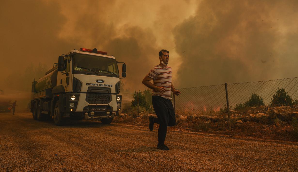 Seorang pria berlari di Desa Sirtkoy yang dilanda kebakaran, dekat Manavgat, Antalya, Turki, Minggu (1/8/2021). Menurut para pejabat, lebih dari 100 kebakaran hutan telah dikendalikan di Turki. (AP Photo)