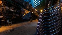 Seorang pria mengenakan masker pelindung melintas di jalanan sepi di kawasan hiburan malam Lan Kwai Fong, Hong Kong (5/5/2020). Kebijakan pemerintah Hong Kong itu membuat gemerlap hiburan malam di Lan Kwai Fong meredup seketika. (AFP/May James)