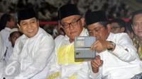 Ketua Umum Partai Golkar Setya Novanto, Aburizal Bakrie dan Idrus Marham (kiri ke kanan) berfoto bersama jelang buka puasa AMPG bersama ribuan anak yatim piatu di Jakarta, Sabtu (18/6). (Liputan6.com/Helmi Fithriansyah)