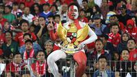 Andi Kiswantoro rela mengecat seluruh bagian tubuhnya dan memegang patung Garuda Pancasila saat mendukung Timnas Indonesia U-16. (Bola.com/Aditya Wany)