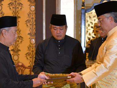 Muhyiddin Yassin (kiri) menerima dokumen dari Raja Sultan Abdullah Sultan Ahmad Shah (kanan) sebelum disumpah sebagai Perdana Menteri Malaysia di Istana Negara, Kuala Lumpur, Minggu (1/3/2020). Muhyiddin Yassin resmi menjadi PM Malaysia. (MASZUANDI ADNAN/MALAYSIA'S DEPARTMENT OF INFORMATION/AFP)