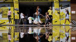 Orang-orang dengan masker melintasi toko resmi Tour de France 2020 di kota Nice, French Riviera, Rabu (26/8/2020). Ajang balap sepeda lintas kota di Prancis ini akan dimulai dari kota Nice pada 29 Agustus hingga 20 September di bawah bayang-bayang 'gelombang kedua' COVID-19. (Kenzo Tribouillard/AFP)
