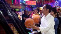 Presiden Joko Widodo dan cucu Jan Ethes Srinarendra menyempatkan diri bermain basket di Sun Plaza Medan, Sumatera Utara, Jumat (24/11). Jokowi tiba di lokasi mengenakan kemeja putih lengan panjang dan celana hitam. (Liputan6.com/Johan Tallo)