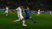 Pemain Yunani, Lazaros Christodoulopoulos berebut bola dengan pemain Kroasia, Domagoj Vida pada laga leg kedua play-off Piala Dunia 2018 di Stadion Karaiskakis, Senin (13/11). Kroasia menang dengan agregat 4-1 atas Yunani. (AP/Thanassis Stavrakis)